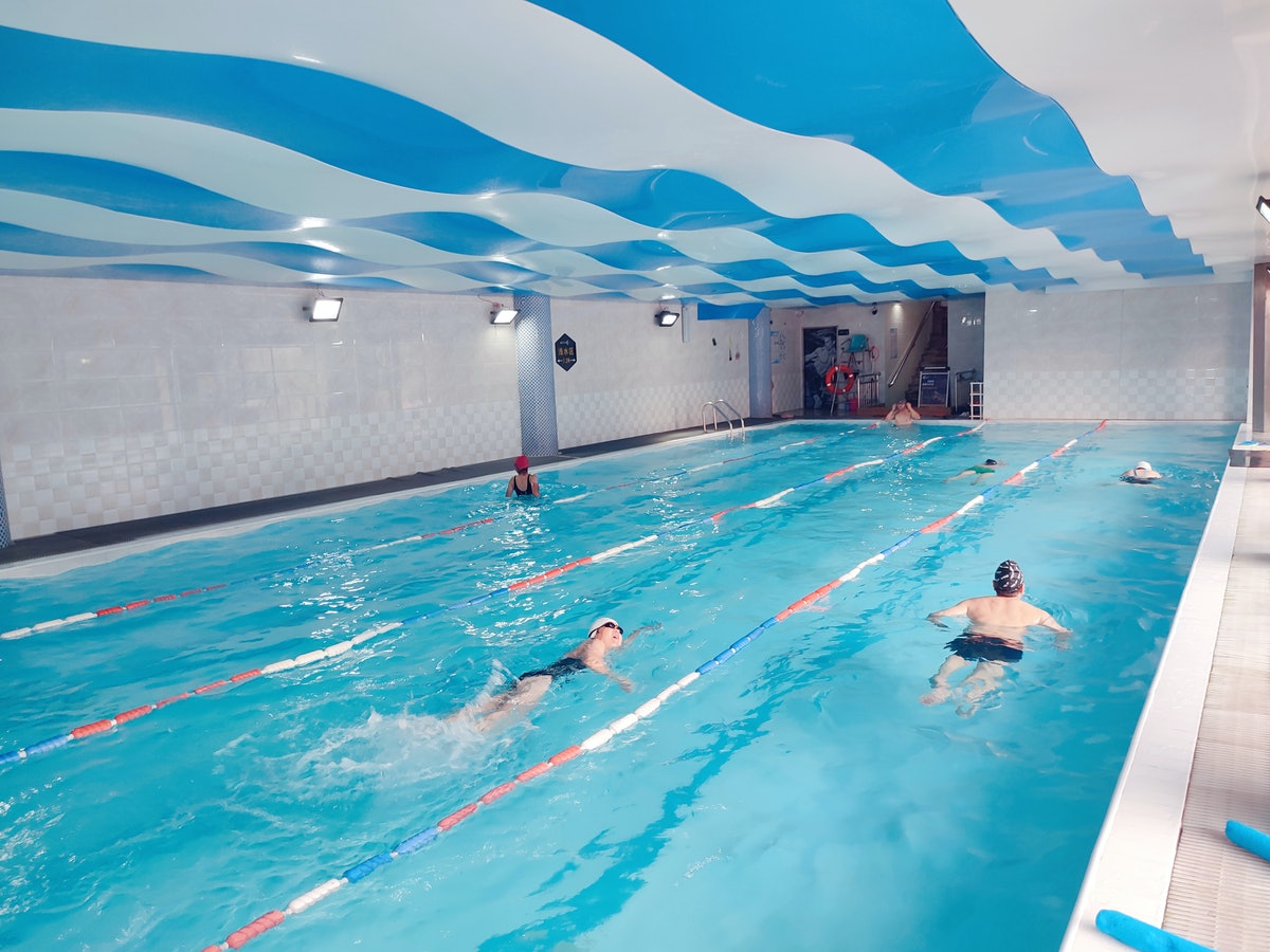 A few swimmers exercise in different lanes of an indoor pool. Swimming is a no-impact form of exercising that is easy on your joints.