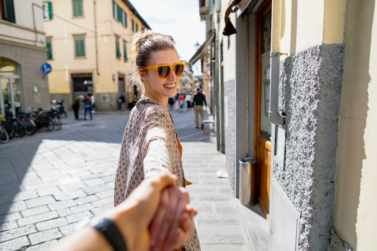 A woman holds hands with her partner while traveling through Italy in a photo that's as cute as a lo...