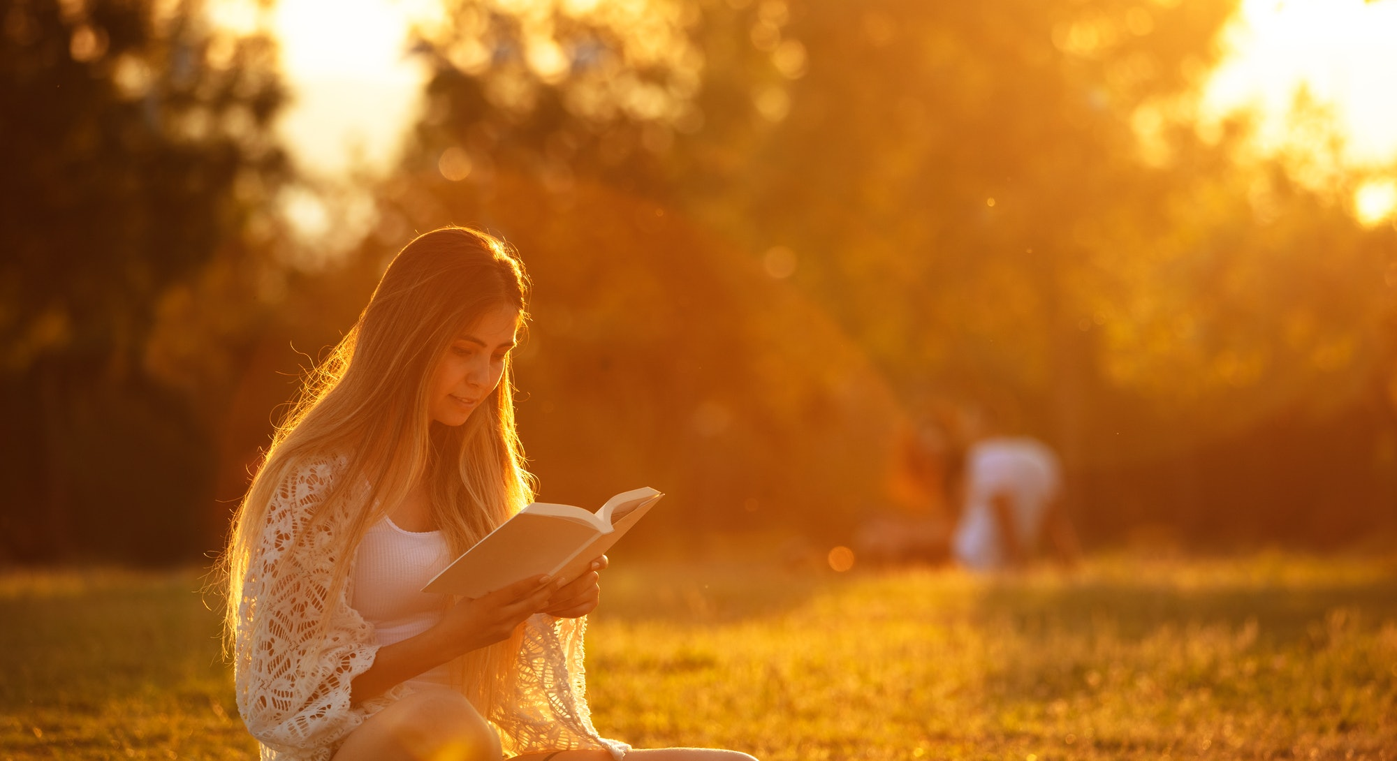 young woman studying on the grass at sunset