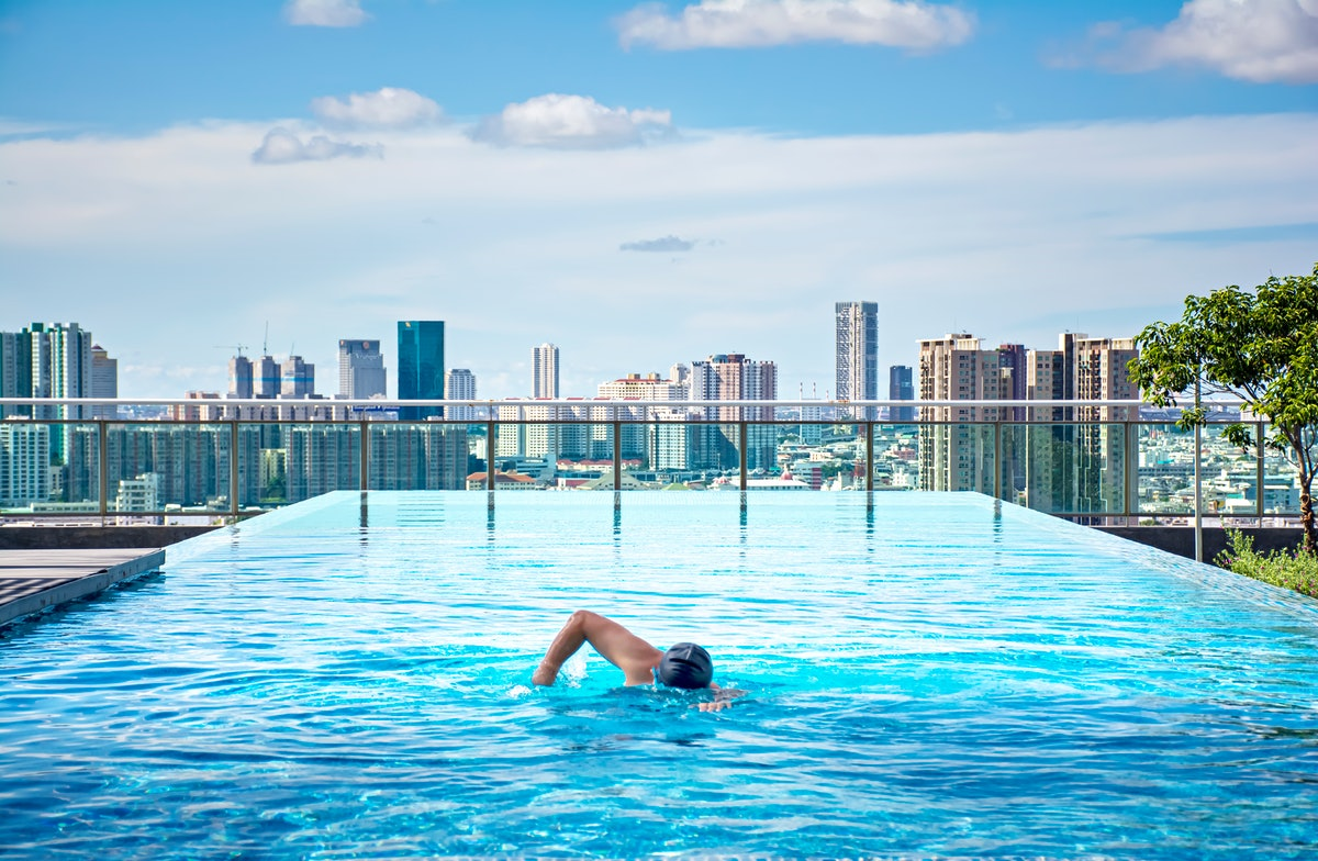 A person swims in a rooftop pool. Swimming requires a lot of mental focus.