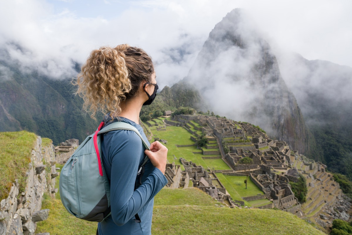 A woman wearing a face mask looks at Machu Picchu from atop a hill.