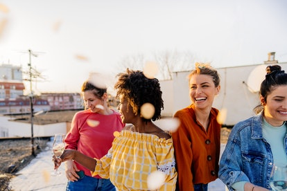 Photo of smiling young women having a great time during the rooftop party; celebrating their friends...