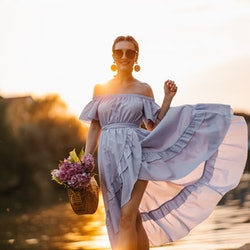 Beautiful young woman in blue romantic swaying dress holding wooden purse with bouquet of chrysanthemums posing at sunset by the river