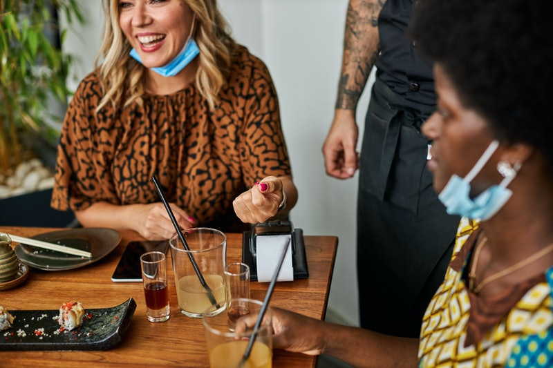 Two friends split the bill in a restaurant. Experts share their tips for how to remind someone to pay you.