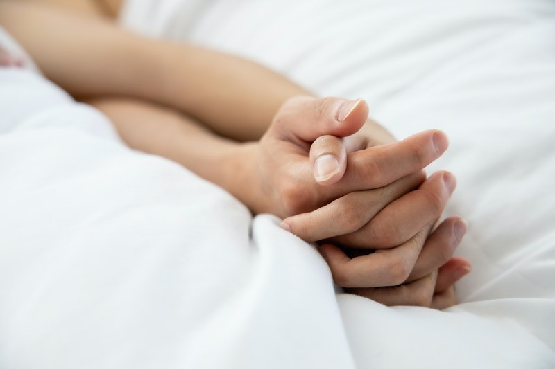 Love emotion concept:  hand of couple love on the white bed
