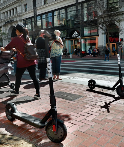 Two Bird scooters parked along Market St. as pedestrians wait at  the crosswalk as seen on Mon. Apri...