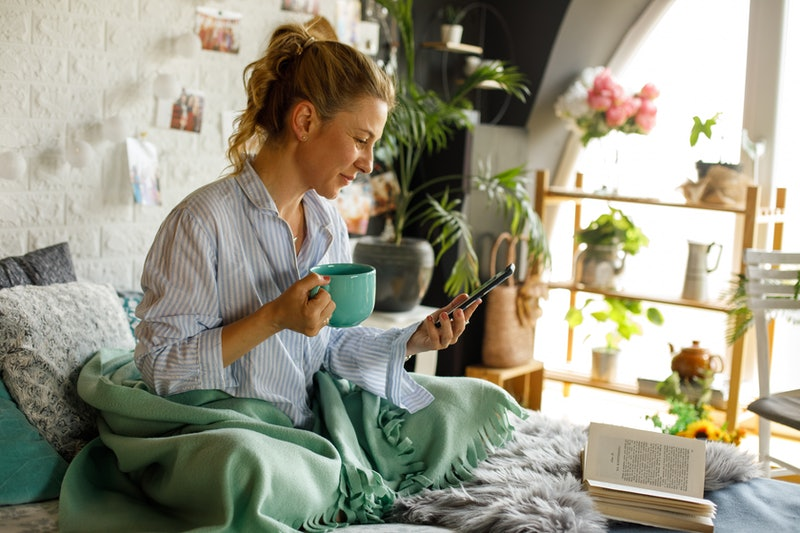 A woman checks her previously liked posts on Instagram while drinking coffee in bed.