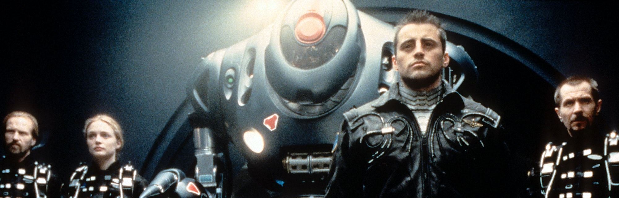 Gary Oldman, William Hurt, Heather Graham and Matt LeBlanc standing with a space machine in a scene ...