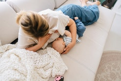 Photo of young woman breastfeeding her baby at home