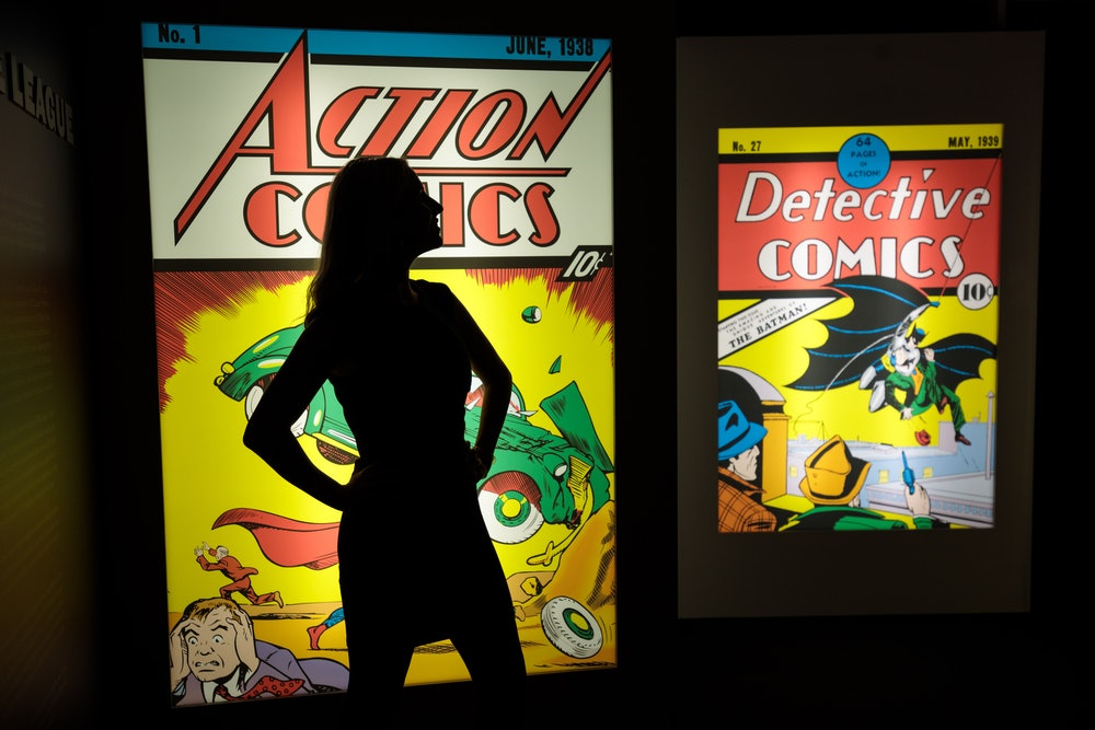 LONDON, ENGLAND - FEBRUARY 22: An employee poses in front illuminated displays of the first comics t...