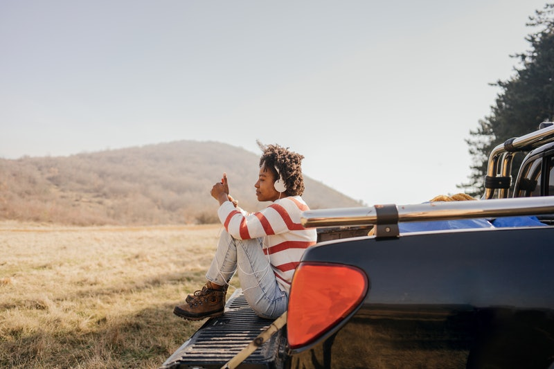 Photo of a young woman on a road trip sitting on pick-up truck texting her family to stay in touch.