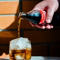 UKRAINE - 2021/04/29: In this photo illustration a Coca-Cola soft drink being poured into a glass wi...