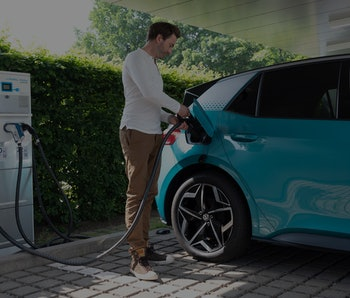 08 June 2021, Saxony, Dresden: A man plugs a charging cable into the filler neck of a VW ID.3 during...