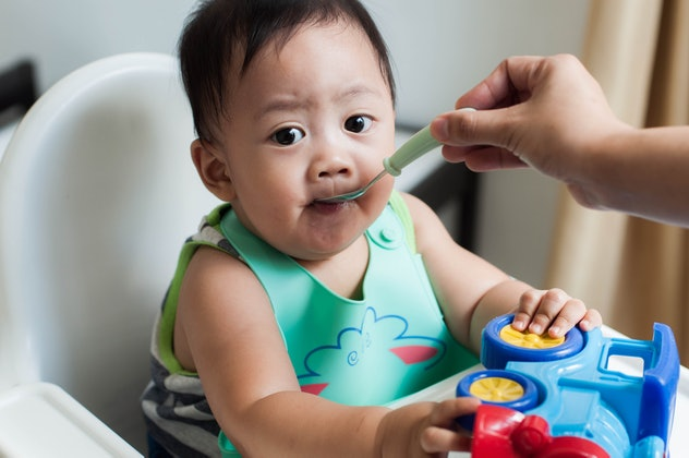 Waist-up candid portrait of a Southeast Asian baby boy eating while sitting on a high chair at home