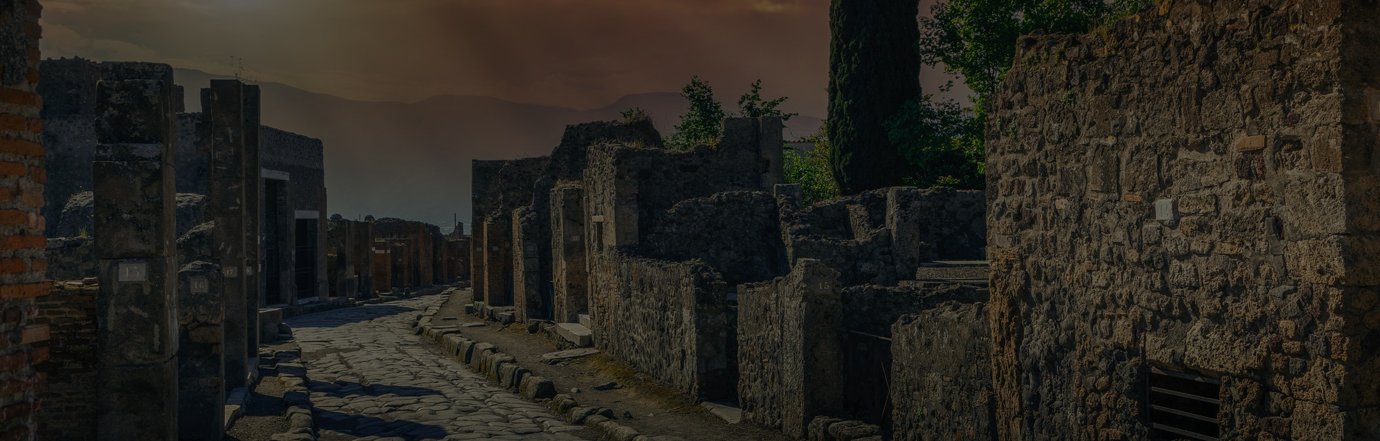 Old stones paved road at sunset in Pompeii Archaeological site.