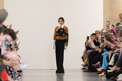 Victoria Beckham on stage following the runway presentation of a new fashion collection. She is stan...