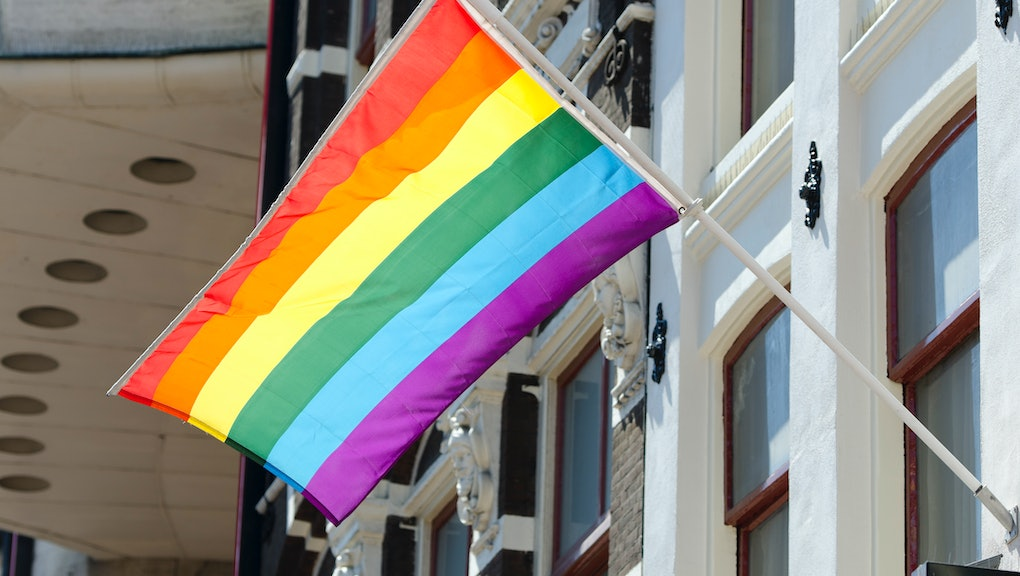 A clean rainbow flag hanging out of a building.