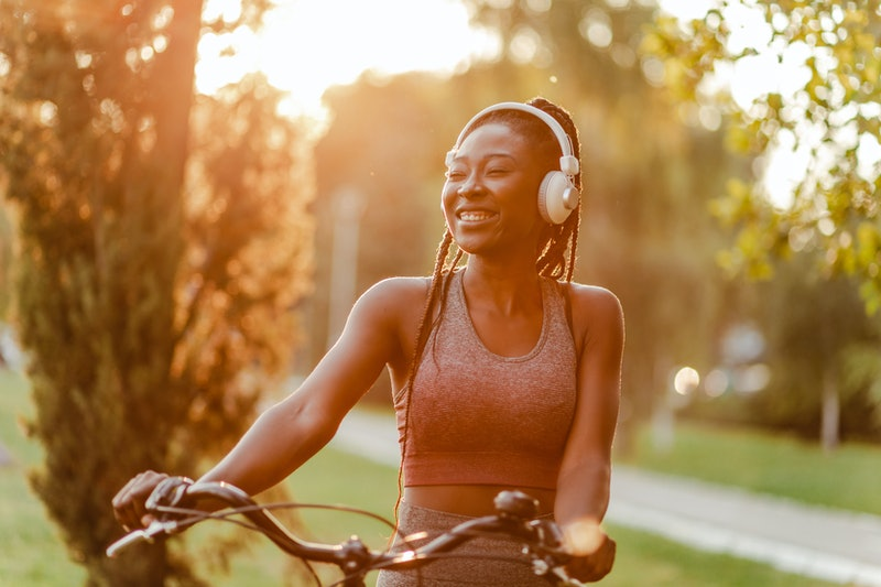 Portrait of a modern smiling African American woman in the park with her bicycle