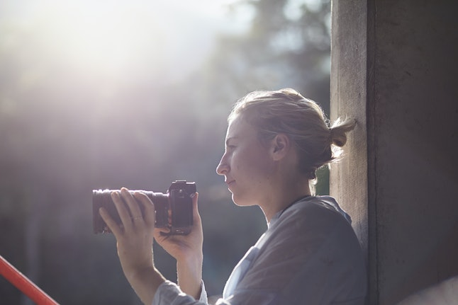 female photographer relaxing in hazy backlight, thinking and relaxing, looks happy and thoughtful