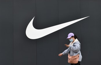 BEIJING, CHINA - MAY 10, 2021 - A pedestrian passes in front of the Nike logo of the Nike flagship store at Wangfujing Pedestrian Street in Beijing, China, May 10, 2021. (Photo credit should read Costfoto/Barcroft Media via Getty Images)