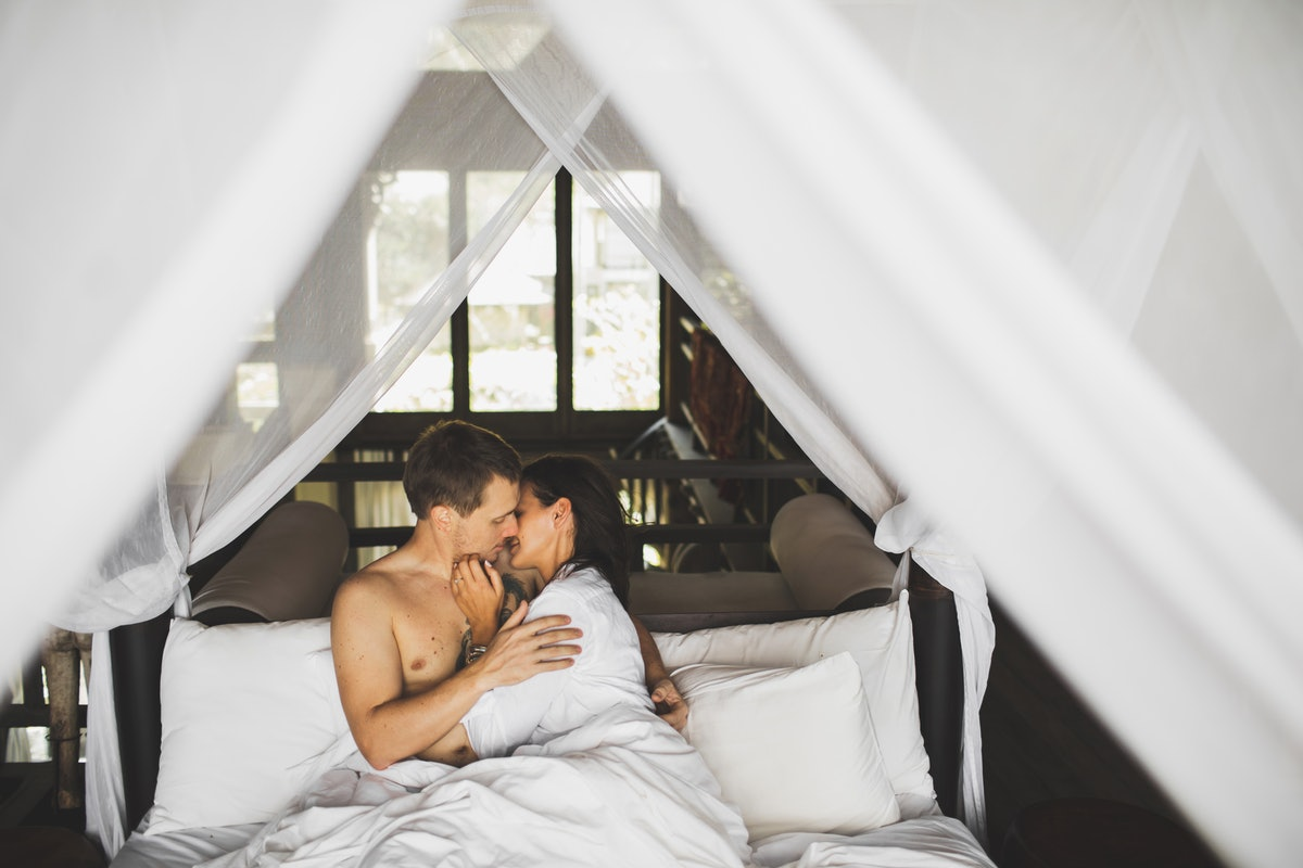Love, desire and passion. Intimate and sensual portrait of young pretty heterosexual couple flirting together. Honeymoon time. Relaxing and enjoying at home bedroom on white linens.