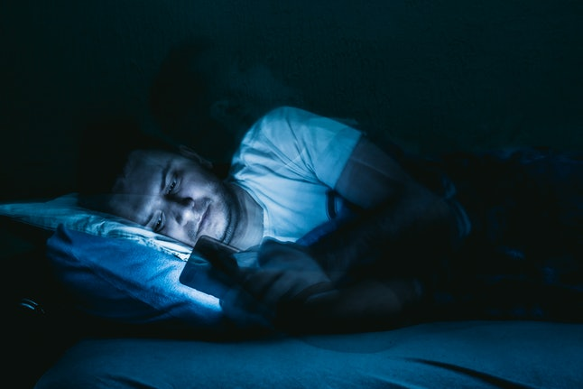 Man lying in bed and using smartphone. Spending time during pandemic lockdown. Coronavirus/Covid-19.