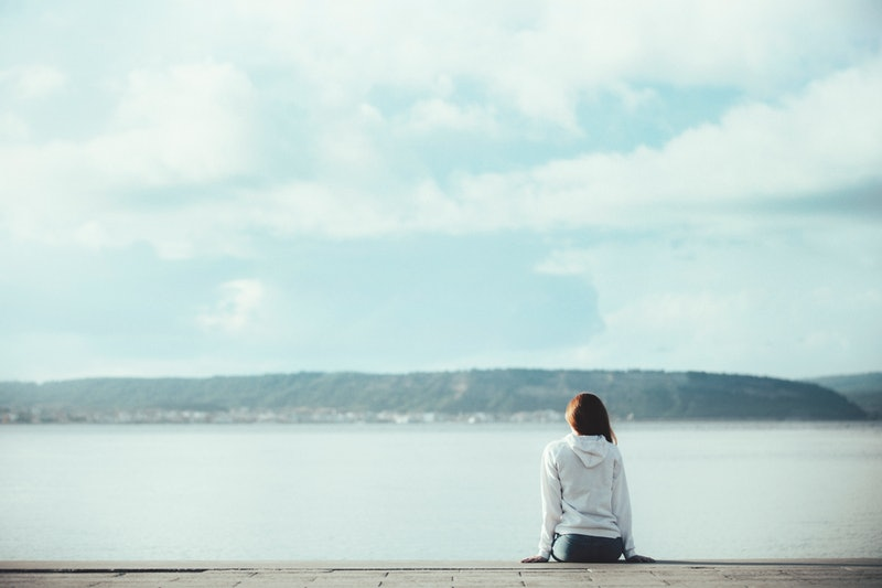 Back view of one teenager girl thinking alone and watching the sea sitting at sea side with the hori...