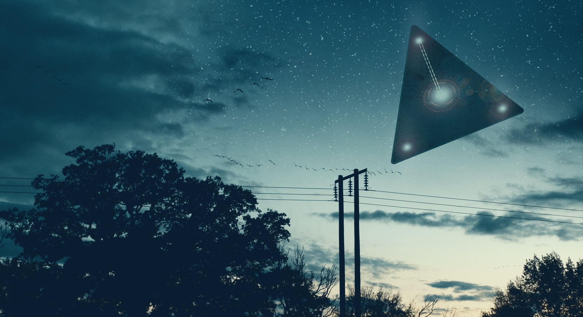 UFO concept. A flying triangle floating above the countryside at night.