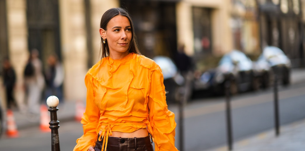 PARIS, FRANCE - JUNE 24: Alice Barbier wears an earring, an orange cropped top with long sleeves and large embroidery and pleats, brown leather pants, a brown leather bag, outside Acne Studios, during Paris Fashion Week - Menswear Spring/Summer 2022, on June 24, 2021 in Paris, France. (Photo by Edward Berthelot/Getty Images)