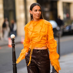 PARIS, FRANCE - JUNE 24: Alice Barbier wears an earring, an orange cropped top with long sleeves and...