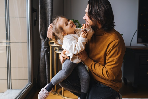 Portrait of father and daughter playing at home, Cute girl lying on happy father back on cozy couch close up, family having fun, enjoying funny activity, leisure time on weekend, hugging and cuddling, relaxing on sofa in living room