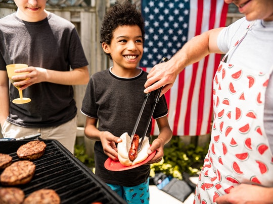 People waiting for burgers at the BBQ grill for outdoor 4th July backyard celebration. Multi racial,...