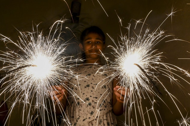 A girl holds sparklers as the Sinhala and Tamil communities celebrate New Year in Colombo on April 1...