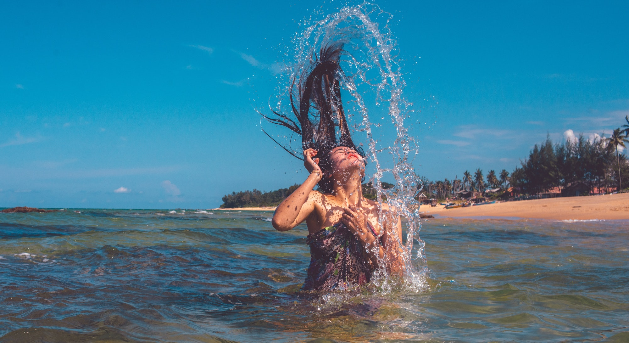 A person tosses their hair over their head as they emerge from the water. Even if you're new to swimming, you can get in some good swimming workouts.