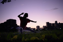 Woman doing taichi in empty city early in the morning. Here's how tai chi vs. yoga compare.