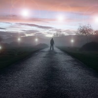 A UFO concept of glowing orbs, floating above a misty winters road just after sunset. With a silhoue...