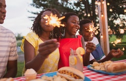 A family sits at a table outside and enjoys a summer barbecue together.