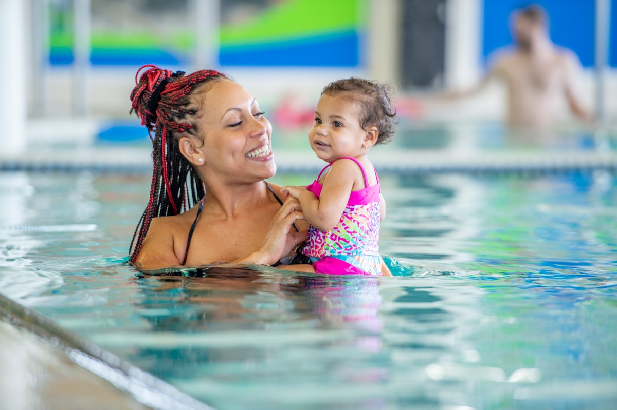 A person smiles while holding their child in a swimming pool. Swimming can be accessible to people of various ages and physical abilities.