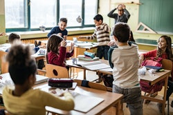 Large group of school kids making chaos during a class in the classroom while their teacher is frustrated about that.