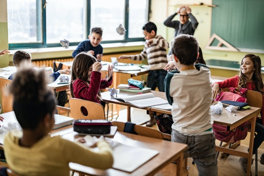Large group of school kids making chaos during a class in the classroom while their teacher is frust...