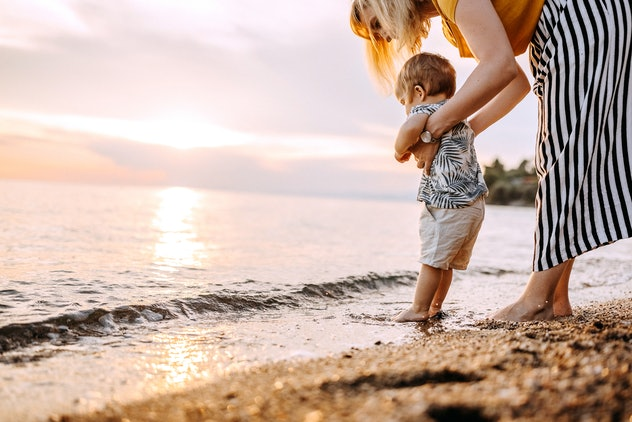 Young mother with little boy enjoying walking in the sea at the sunset