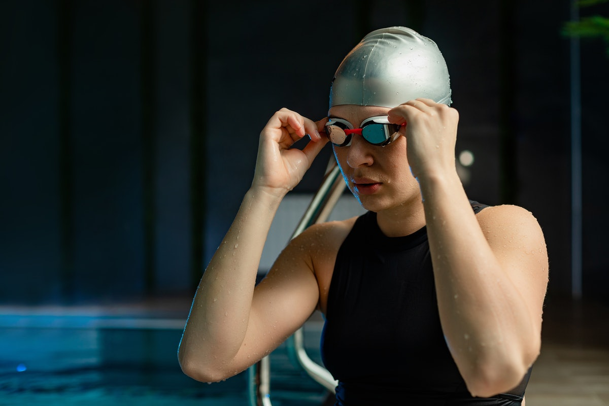 A person puts their goggles on as they get into a swimming pool. Taking even one swimming lesson from a certified instructor can help you learn to swim safely.