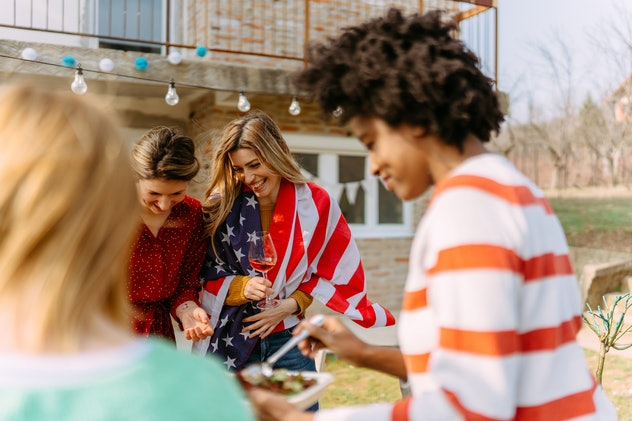 Photo of a small group of friends celebrating Independence day together by throwing an outdoor barbe...