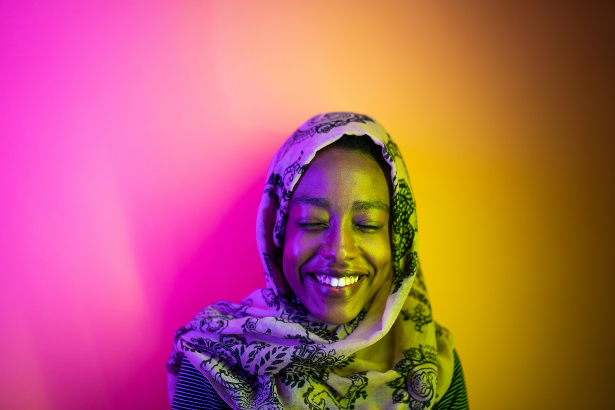 Young woman wearing a hijab, under neon lights, having the best week of July 5, 2021, per her zodiac sign.