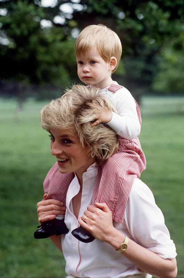 Princess Diana carries Prince Harry on her shoulders.