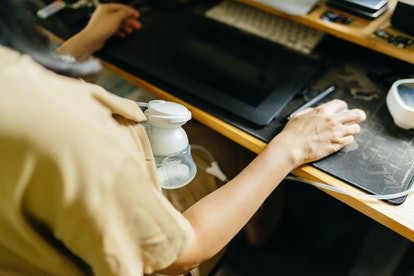 woman wearing a breast pump while working at computer