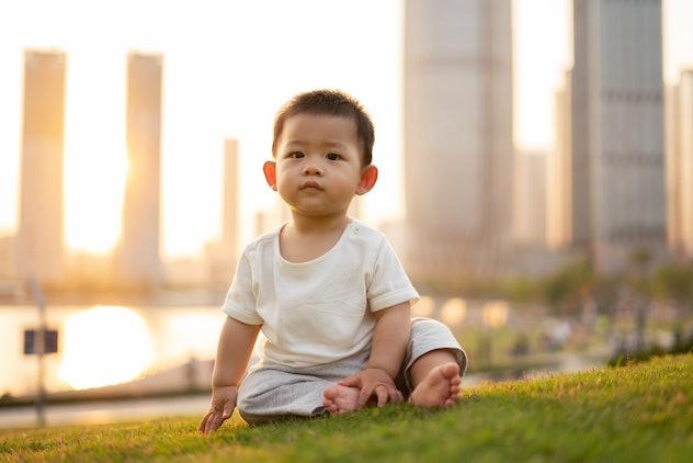 toddler boy sitting in park