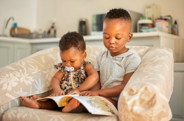 Small brother and sister watching children's educational books while sitting together on an armchair...
