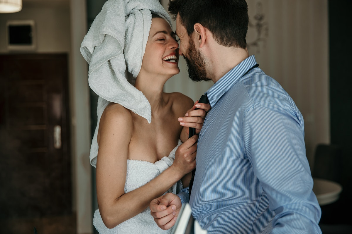 A beautiful woman helping her husband to get ready for work, morning preparation of young married couple.