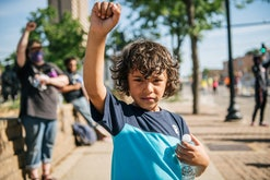 A boy raises his fist in the air as protesters rally in front of the 2nd Precinct Police Station dur...